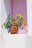 Blomkruka med en grek och en engelsk flagga förutom ett hus mot en rosa dörr Royaltyfri Foto
