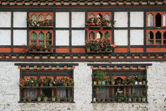Blomkrukor är pålagda kanten av fönstren av ett hus (Bhutan) Arkivfoto