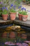 Blomkrukor & reflexioner, Hidcote säteriträdgård som gå i flisor Campden, Gloucestershire, England Arkivbilder