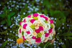 Blomma bröllopbuketten av vit- och rosa färgblommor med guld- vigselringar av brudar, på ett grönt gräs med blommor Royaltyfria Bilder