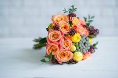 Blomma buketten med orange rosor och gulna ranunculusen Royaltyfri Bild