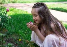 Blomma för tulpan för liten flickalukt röd på vårtid arkivfoto