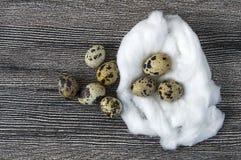 Blomma-formade fega ägg och vaktelägg För ägg- och vakteläggställningen för vit den fega sidan - förbi - sid på ett trägolv, Royaltyfria Bilder