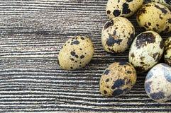 Blomma-formade fega ägg och vaktelägg För ägg- och vakteläggställningen för vit den fega sidan - förbi - sid på ett trägolv, Royaltyfria Foton