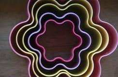 Blomma formade kakaformer i neonfärger fotografering för bildbyråer