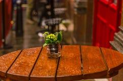 Blomma i en krus på restaurangtabellen efter regn Arkivfoton