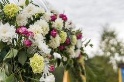 Blomma som en garnering på ett bröllop Blom- träbåge med den gula torkduken och nya vita blommor med gröna sidor på a arkivfoton