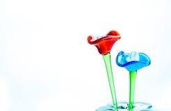 Blomma som göras av exponeringsglas i röd och blå färg i vas på vitbaksida Arkivfoton