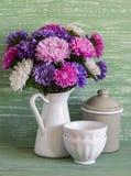 Blommaaster i en vit emaljerad kanna och tappninglerkärl - keramisk bunke och emaljerad krus, på en blå träbakgrund Fotografering för Bildbyråer