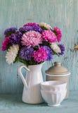 Blommaaster i en vit emaljerad kanna och tappninglerkärl - keramisk bunke och emaljerad krus, på en blå träbakgrund Royaltyfria Bilder