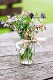 Blommabukett i den glass kruset på lantlig wood bakgrund Royaltyfria Foton