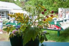 Blommabukett i en exponeringsglasplanterkrus som föreställas på en utsmyckad vit tabell royaltyfria bilder