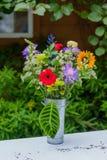 Blommabukett i en metallvas Fotografering för Bildbyråer