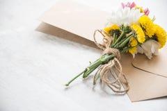 Blommabukett med kortanmärkningen och kuvert på en vit wood lantlig bakgrund Arkivbild