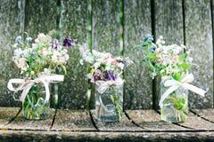 Blommabuketter i exponeringsglas skorrar på lantlig wood bakgrund Arkivfoto