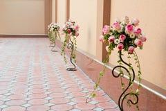 Blommabuketter i vases nära en vägg Arkivfoto