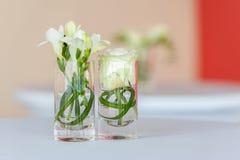 Blommagarnering i små exponeringsglas arkivfoto