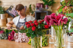 Blommaleveransen shoppar och den unfocused blomsterhandlaren Arkivfoto