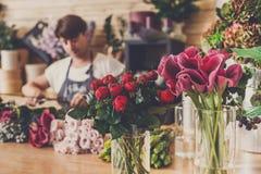 Blommaleveransen shoppar och den unfocused blomsterhandlaren Arkivbilder