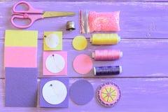 Blomman av filtcirklar och pärlor, kulöra filtcirklar och ark, sax, pappers- mallar, tråden, visare, pryder med pärlor på en tabe Arkivfoton