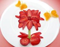 Blomman och fjärilar för idérik fruktbarnefterrätt bildar den röda Arkivbilder