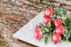 Blomman som är röd på tabellen som är forntida på bakgrunden, är den gamla väggen Royaltyfri Bild