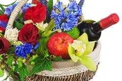 Blommaordning av rosor, orkidér, frukter och flaskan av vin Royaltyfria Bilder