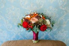 Blommaordning för ett bröllopparti Buketten av rosa rosor, röda pioner och andra blommor på den blåa väggen Royaltyfri Fotografi
