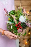 Blommaordning i händer av blomsterhandlaren på etappen av avslutning royaltyfria foton