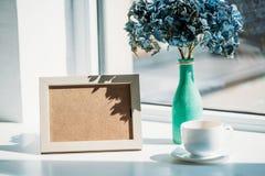 blommar den övre sikten för slutet av den tomma fotoramen, koppen kaffe och buketten av hortensia i vas på fönsterbräda royaltyfria bilder
