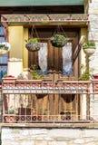 Blommar den grekiska balkongen för härlig tappning med den hängande krukan Royaltyfri Bild