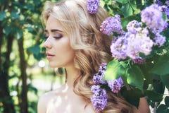 Blommar den härliga unga kvinnan för utomhus- mode som omges av lilan, sommar Lila buske för vårblomning Stående av en blond flic Royaltyfri Foto