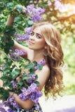 Blommar den härliga unga kvinnan för utomhus- mode som omges av lilan, sommar Lila buske för vårblomning Stående av en blond flic Royaltyfri Bild