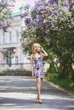 Blommar den härliga unga kvinnan för utomhus- mode som omges av lilan, sommar Lila buske för vårblomning Stående av en blond flic royaltyfria foton
