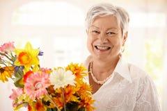 blommar den lyckliga kvinnan för holdingståendepensionären Arkivfoton