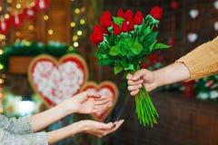 Blommar den närvarande flickan för grabben på dag för valentin` s Fotografering för Bildbyråer