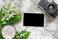 Blommar den retro kameran för tappning med den tomma foto- och kaffekoppen med liljekonvaljen Arkivfoto