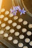 Blommar den svarta tappningskrivmaskinen för antikviteten med den blåa romantiska våren arkivbilder