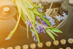 Blommar den svarta tappningskrivmaskinen för antikviteten med den blåa romantiska våren royaltyfri foto