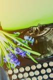Blommar den svarta tappningskrivmaskinen för antikviteten med den blåa romantiska våren arkivfoto