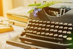 Blommar den svarta tappningskrivmaskinen för antikviteten med den blåa romantiska våren royaltyfri bild