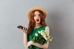 Blommar den unga chockade kvinnan för rödhåriga mannen att prata vid telefonen royaltyfria foton