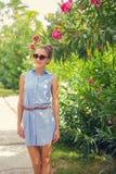 blommar flickaståenden blå klänningmaike Royaltyfri Foto