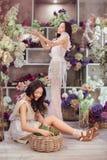 Blommar lyckligt arbete för härliga asiatiska kvinnablomsterhandlare i blommalager med mycket vår Royaltyfria Foton