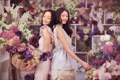 Blommar lyckligt arbete för härliga asiatiska kvinnablomsterhandlare i blommalager med mycket vår Arkivfoton