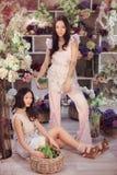 Blommar lyckligt arbete för härliga asiatiska kvinnablomsterhandlare i blommalager med mycket vår Arkivfoto