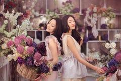 Blommar lyckligt arbete för härliga asiatiska kvinnablomsterhandlare i blommalager med mycket vår Arkivbilder
