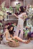 Blommar lyckligt arbete för härliga asiatiska kvinnablomsterhandlare i blommalager med mycket vår Royaltyfri Bild