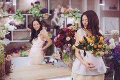 Blommar lyckligt arbete för härliga asiatiska kvinnablomsterhandlare i blommalager med mycket vår Royaltyfri Fotografi