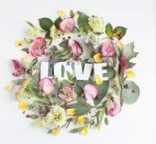 Blommasammansättning med ordet FÖRÄLSKELSE Royaltyfri Fotografi